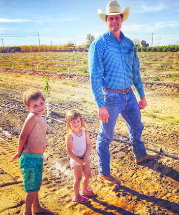 Mark with his son Corban and daughter Avery teaching them about almonds